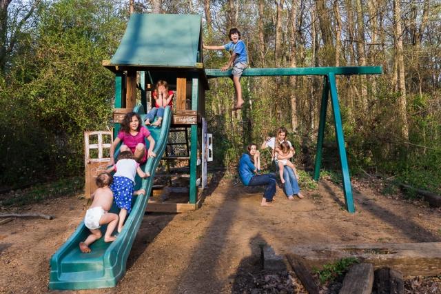 eight-children-playing-on-backyard-playset-large-family-full-sun